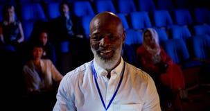 Hombre de negocios afroamericano que asiste a seminario del negocio en el auditorio 4k almacen de video