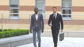 Hombre de negocios afroamericano que camina en la calle cerca del edificio de oficinas metrajes