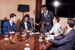 Hombre de negocios afroamericano que da la presentación a los socios imagenes de archivo