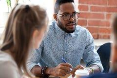 Hombre de negocios afroamericano que habla con el colega en el informe imágenes de archivo libres de regalías