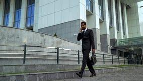 Hombre de negocios afroamericano que habla en el teléfono, subrayado y con exceso de trabajo, plazo fotos de archivo