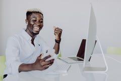 Hombre de negocios afroamericano que hace las manos del witn del dinero encima del triunfo en la oficina fotos de archivo