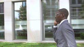 Hombre de negocios afroamericano que hace una llamada de teléfono móvil - personas negras metrajes
