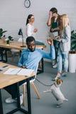 hombre de negocios afroamericano que juega con el perro en el correo y los compañeros de trabajo que tienen reunión detrás en mod imagen de archivo