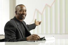 Hombre de negocios afroamericano que presenta beneficios Foto de archivo libre de regalías