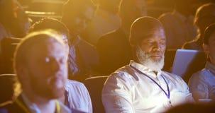 Hombre de negocios afroamericano que usa el ordenador portátil durante seminario en el auditorio 4k almacen de metraje de vídeo