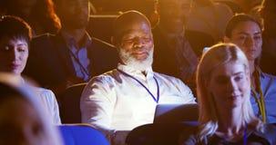 Hombre de negocios afroamericano que usa el ordenador port?til durante seminario en el auditorio 4k almacen de video