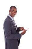 Hombre de negocios afroamericano que usa una tableta táctil sobre blanco Imagenes de archivo