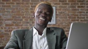 Hombre de negocios afroamericano rubio feliz joven que se sienta en oficina y que mira la cámara, la risa y la sonrisa almacen de metraje de vídeo