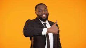 Hombre de negocios afroamericano seguro de sí mismo que hace el gesto de los pulgares-para arriba, buen servicio almacen de video