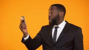 Hombre de negocios afroamericano sorprendido satisfecho con la aplicación móvil, herramientas metrajes