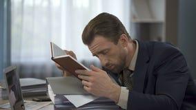 Hombre de negocios agotado que mira la lista larga en cuaderno y que la pone en la cabeza almacen de metraje de vídeo