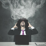 Hombre de negocios agotador con humo sobre su cabeza Imagen de archivo