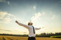 Hombre de negocios agradecido con los brazos abiertos en el campo Imagen de archivo