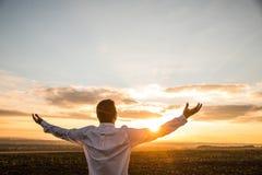 Hombre de negocios agradecido con los brazos abiertos en el campo en puesta del sol Imagen de archivo libre de regalías