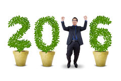 Hombre de negocios alegre con los números formados árboles 2016 Imágenes de archivo libres de regalías