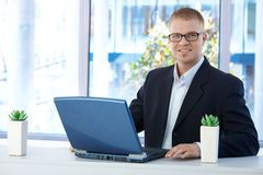 Hombre de negocios alegre en oficina Foto de archivo
