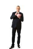 Hombre de negocios alegre integral que lleva a cabo el piggybank Imagen de archivo