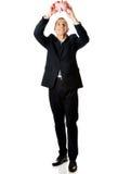 Hombre de negocios alegre integral que lleva a cabo el piggybank Foto de archivo