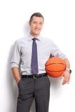 Hombre de negocios alegre joven que lleva a cabo un baloncesto Imágenes de archivo libres de regalías