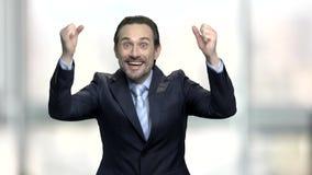 Hombre de negocios alegre que aprieta sus puños en el entusiasmo almacen de metraje de vídeo