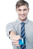 Hombre de negocios alegre que da su tarjeta de crédito fotografía de archivo