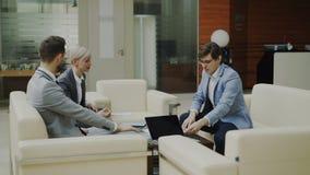 Hombre de negocios alegre que discute informes financieros con los socios comerciales que se sientan en el sofá en pasillo modern