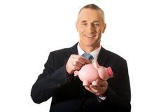 Hombre de negocios alegre que lleva a cabo el piggybank Imagenes de archivo