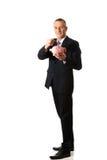 Hombre de negocios alegre que lleva a cabo el piggybank Fotografía de archivo libre de regalías