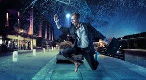 Hombre de negocios alegre que salta con un paraguas Fotos de archivo libres de regalías