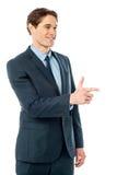 Hombre de negocios alegre que señala lejos imagen de archivo libre de regalías