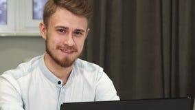 Hombre de negocios alegre que sonríe a la cámara mientras que trabaja en el ordenador foto de archivo