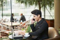 Hombre de negocios alegre que trabaja en la tabla del café imagen de archivo