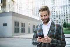 Hombre de negocios alegre usando el teléfono móvil en la calle Foto de archivo libre de regalías