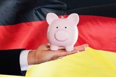 Hombre de negocios alemán que lleva a cabo el piggybank Imagen de archivo