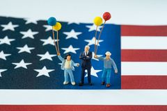 Hombre de negocios americano feliz miniatura con la familia que sostiene el globo Imágenes de archivo libres de regalías