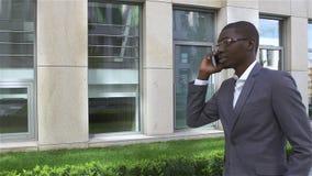 Hombre de negocios americano que habla en el teléfono celular, colocándose delante de su oficina Cámara lenta almacen de metraje de vídeo