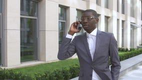 Hombre de negocios americano que hace una llamada de teléfono móvil - personas negras almacen de video