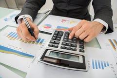 Hombre de negocios Analyzing Graph And que usa la calculadora Foto de archivo
