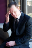 Hombre de negocios ansioso con un dolor de cabeza Imagen de archivo libre de regalías