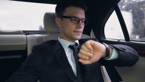 Hombre de negocios ansioso joven atrasado para el vuelo, mirando el reloj, tráfico en ciudad almacen de metraje de vídeo