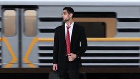 Hombre de negocios ansioso que comprueba tiempo en la estación de tren almacen de video