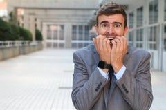 Hombre de negocios ansioso que muerde sus clavos aislados imagenes de archivo