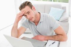 Hombre de negocios ansioso usando el ordenador portátil y el cuaderno Imagen de archivo