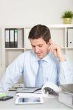 Hombre de negocios apuesto con el dispositivo de la calculadora Fotografía de archivo