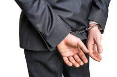 Hombre de negocios arrestado en esposas con las manos detrás detrás imagenes de archivo