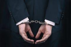 Hombre de negocios arrestado en esposas con las manos detr?s detr?s imagenes de archivo