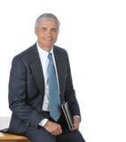 Hombre de negocios asentado en el borde de su escritorio foto de archivo libre de regalías