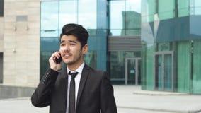 Hombre de negocios asiático acertado que hace llamadas de teléfono felices almacen de video