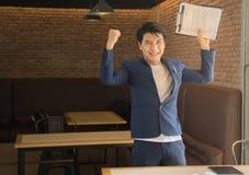 Hombre de negocios asiático alegre ganar y tener éxito el triunfo con las manos aumentadas imagen de archivo libre de regalías